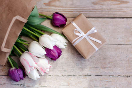 Spring gift and flowers. Tulips and box with present at wooden background. Blooming bouquet in kraft shopping bag. Flat lay. Copy space. 写真素材