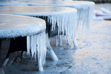 Icicles on tables in cafe outside. Abnormal cold weather. Winter sea. Ice and frozen floor. 写真素材