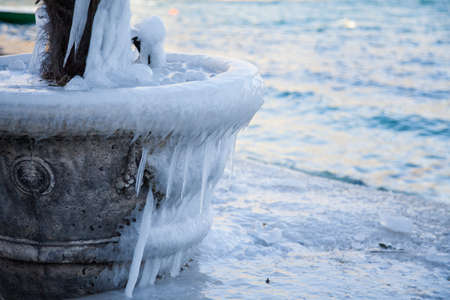 Icicles on flowerpot with palm tree. Cold winter sea with blue waves. Icy-covered stone pier. 写真素材