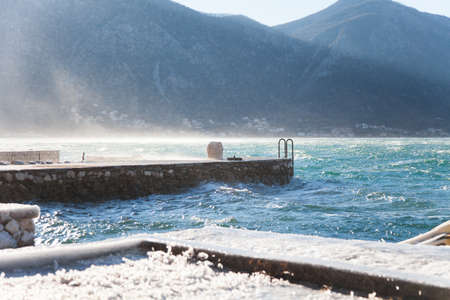 Cold stormy winter sea with blue waves near mountains. Icy-covered stone pier. Windy weather.