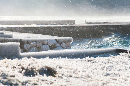 Cold winter sea with blue waves and snowstorm. Frozen stone pier, grass with ice. Windy weather.