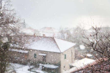 Winter blurred background. Snowfall and blizzard in countryside with houses and white snowy tiled roofs.
