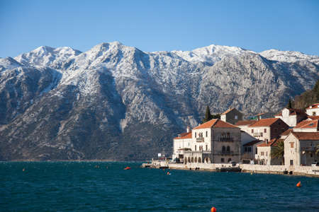 Winter in Montenegro. Beautiful old town Perast in the Bay of Kotor with snow peaks of mountains, blue cold the Adriatic Sea, ancient architecture, stone houses and tiled roofs. 写真素材