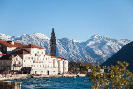 Winter in Montenegro. Perast in the Bay of Kotor with snow peaks of mountains, blue cold the Adriatic Sea, old town with ancient architecture, stone houses and tiled roofs. 写真素材