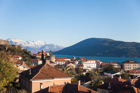 Tiled roofs of old town at background of beautiful winter nature. Montenegro, Herceg Novi in the Bay of Kotor with snow peaks of mountains, blue cold the Adriatic Sea, ancient architecture and houses.