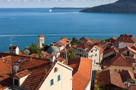 Montenegro, Herceg Novi. Tiled roofs of old town at background of the Adriatic Sea, mountains, cruise liner. Ancient mediterranean architecture.