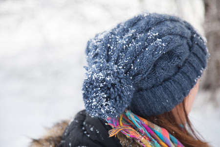 Winter concept. Knitted blue hat with pompon is covered with snow and snowflakes. Girl is in snowy forest or wood.