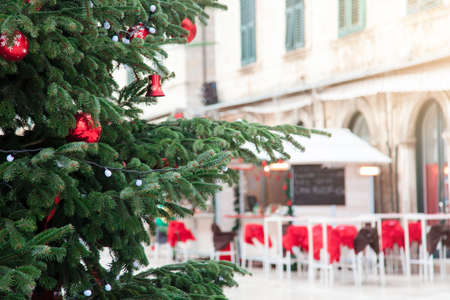 Christmas market outside. Christmas tree with red ornaments. Street cafe in old town. Cozy festive atmosphere in Dubrovnik, Croatia.