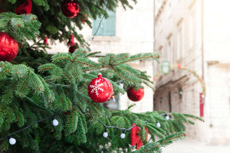 Christmas tree with red balls, baubles and white ornaments in european streets of old town. Cozy authentic festive atmosphere in Dubrovnik, Croatia. 写真素材