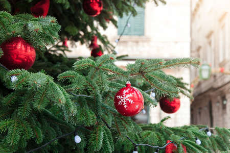Christmas tree with red balls, baubles and white ornaments in ancient streets of old town. Cozy authentic festive atmosphere in Dubrovnik, Croatia. 写真素材