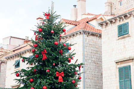 Christmas tree with red ornaments, bows, balls outside. Street decoration in old town near houses and architecture with tiled roofs, wooden shutters. Authentic festive atmosphere in Dubrovnik Croatia 写真素材