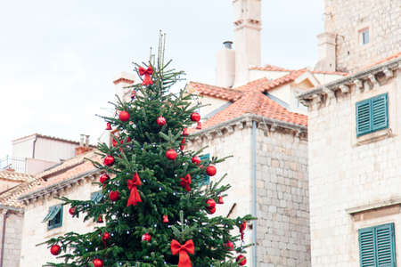 Christmas tree with red ornament, bows, baubles outside. Street decoration in old town near houses and architecture with tiled roofs, wooden shutters. Authentic festive atmosphere in Dubrovnik Croatia
