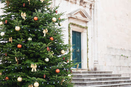 Christmas tree with golden, orange ornaments, baubles, bows outdoors in old town with ancient architecture. Authentic festive atmosphere in Dubrovnik Croatia