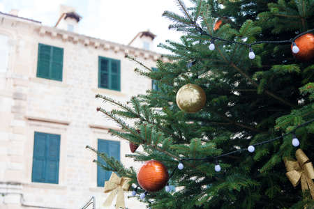 Christmas tree with golden, orange ornaments, baubles, bows outside in old town with ancient architecture, window with shutters. Authentic festive atmosphere in Dubrovnik, Croatia. 写真素材