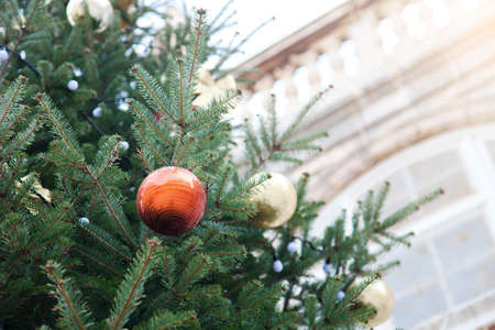 Christmas tree and orange bauble with golden ornaments outside at background of old town architecture. Authentic festive atmosphere in Italy. 写真素材