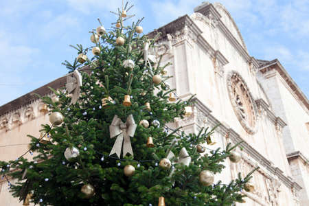 Christmas tree with golden bows, yellow ornaments and baubles in old town near cathedral. Authentic festive atmosphere in streets of Dubrovnik, Croatia 写真素材