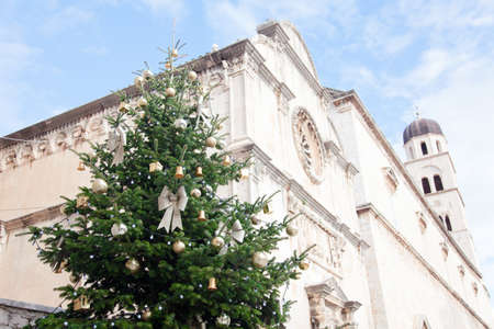 Christmas tree with golden, yellow ornaments, baubles, silver bows in old town with ancient architecture, cathedral, church. Authentic festive atmosphere in streets of Dubrovnik, Croatia