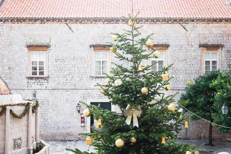 Christmas tree with golden, orange ornaments, baubles, bows outside in old town near ancient building with tiled roof and windows. Authentic festive atmosphere in Dubrovnik Croatia