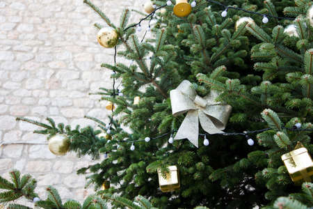 Christmas tree with silver bows, golden ornaments outside at background of stone building wall. 写真素材
