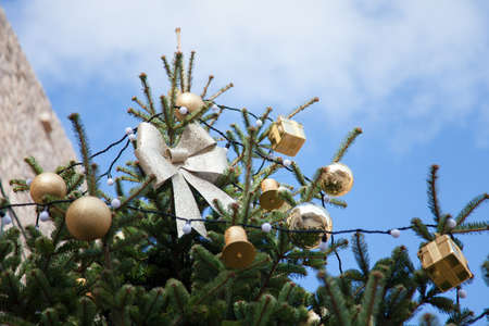 Christmas tree with silver bows, golden ornaments outside at background of blue sky.