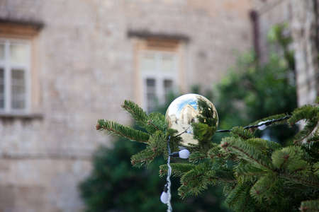 Christmas tree with golden boll outside in old town. 写真素材