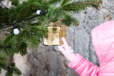 Kid is touching golden gift on Christmas tree outside. New Year street decoration.