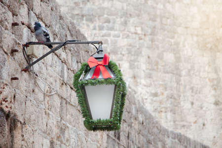 Street light with Christmas decoration, green garland and red bow on stone wall in old town outside.