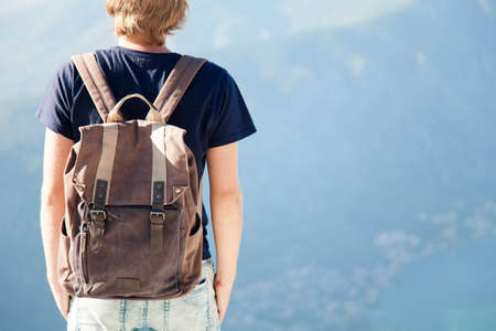 Traveler with backpack in mountains. Tourist at blue background. Young man enjoying traveling, summer vacation, adventure. Lifestyle moment. Rear view. Close up. Copy space.