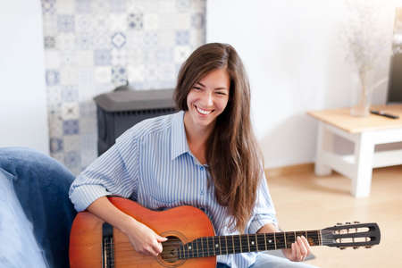 Young woman plays guitar. Happy girl enjoying music. Female musician smiling in living room at home. 写真素材
