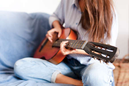 Young woman plays guitar. Happy girl enjoying music. Female musician smiling in living room at home. Close up.