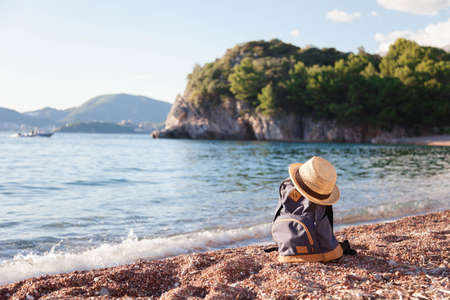 Travel backpack and straw hat at sea beach. Traveler bag at beauriful shoreline. Concept of enjoying traveling, summer vacation, trip, outdoor adventure. Copy space.