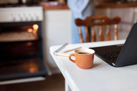 Workplace with cup of coffee, laptop, and notebook. Freelancer home office in cozy kitchen. Concept of female business, working woman, housekeeping and using oven. Close up. 写真素材