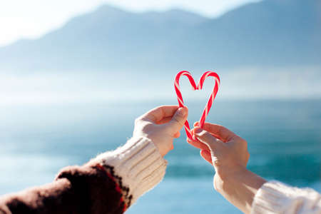 Two candy canes in heart shape. Hands hold Christmas sweets at blue background. Concept of love, romantic holidays, Valentines Day. Happy couple at winter sea beach by mountains outdoors. Copy space. 写真素材
