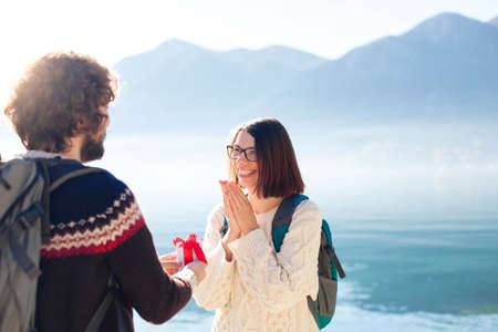 Young man proposing to woman and giving gift box. Happy couple of travelers at winter sea beach by mountains. Happy students celebrate engagement outdoor. Romantic marriage proposal. Lifestyle moment.