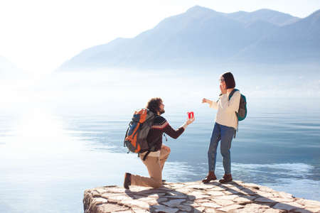 Young man proposing to woman on his knee and giving gift box. Couple at winter sea beach by mountains. Romantic marriage proposal. Lifestyle moment. Happy travelers celebrate engagement outdoor. 写真素材