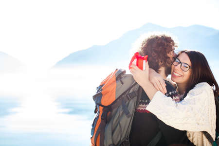 Young man giving gift box to smiling woman. Couple in love hugging and embracing at sea beach by mountains outdoor. Happy travelers celebrate engagement or holiday. Lifestyle moment. Copy space. 写真素材