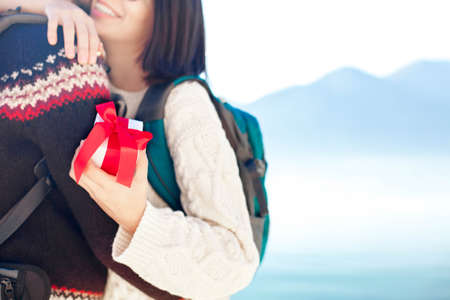 Young woman and man holding gift box. Couple in love hugging and embracing at sea beach by mountains outdoor. Happy travelers celebrate engagement or holiday. Copy space. Close up of hands.