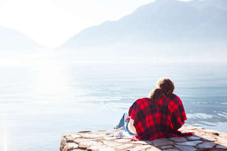 Couple in love hugging at winter sea beach. Young man and woman sitting together in red plaid on pier by blue lake and mountains. Romantic moment, relaxation. Copy space. Rear view.