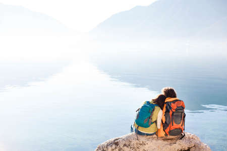 Couple travelers with hiking backpacks at sea beach. Tourists by blue lake and mountains. Young man and woman enjoying traveling, adventure, relaxation, silence and calmness. Copy space. Rear view.