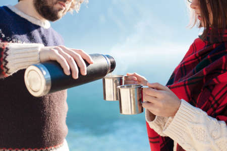 Couple of travelers drink coffee. Winter picnic at sea beach. Man pouring tea from flask. Woman holding metal cups with steamy beverage.