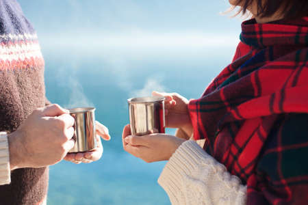Couple in love drink coffee. Winter picnic at sea beach. Travelers hold camping cups with steamy tea. Man and woman enjoying nature, togetherness. Romantic lifestyle moment. Close up of hands.