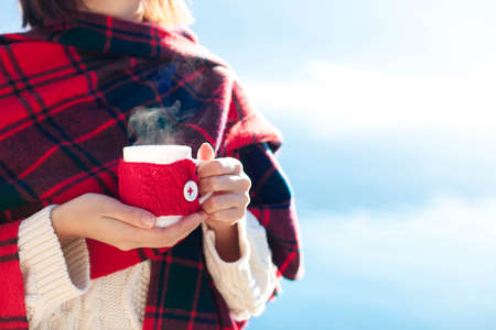 Woman drinking coffee at sea beach. Winter picnic. Girl in red plaid enjoying calm nature, morning breakfast, relaxation. Female hands holding cup of steamy tea. Copy space. Close up.