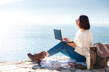 Freelancer workplace at sea beach. Young woman working in traveling from outdoor office at nature. Girl traveler using laptop and Internet and sitting on pier. Successful female business. Copy space.