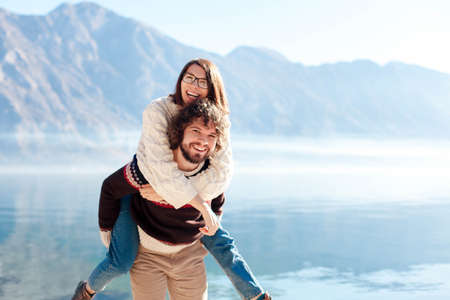 Happy couple in love hugging at winter sea beach. Travelers smiling by blue mountains and lake. Young man giving woman piggyback in vacation, outdoor adventure. Romantic lifestyle moment. Copy space