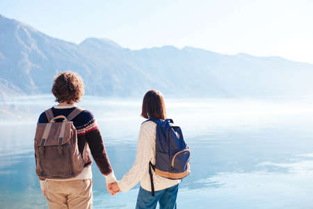 Couple travelers hold hands at winter sea beach. Tourists with backpacks by blue mountains. Young man and woman enjoying traveling, vacation, adventure. Lifestyle moment. Copy space. Rear view. 写真素材
