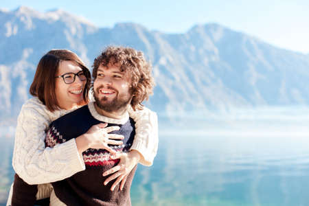 Happy couple in love hugging at winter sea beach. Travelers smiling by blue mountains and lake. Young man and woman together in vacation, outdoor adventure. Romantic lifestyle moment. Copy space 写真素材
