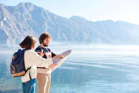 Couple travelers using map at winter sea beach. Happy tourists with backpacks by blue mountains. Young adults man and woman enjoying travel, vacation, adventure. Lifestyle moment. Copy space.