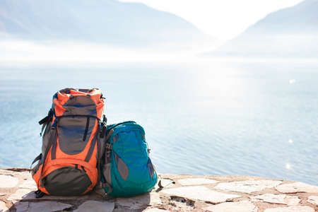 Camping backpacks on sea beach. Concept of travel, vacation, active tourism, hiking, outdoor adventure. Nature background of amazing view with blue lake, mountains. 写真素材