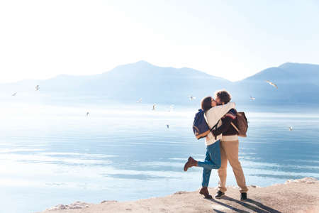 Young couple in love hugging and kissing at winter sea beach. Travelers at blue background of mountains and seagulls. Happy man and woman in vacation, adventure. Romantic lifestyle moment. Copy space