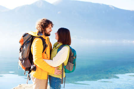 Travelers with hiking backpacks at winter sea beach. Young couple in love hugging and smiling by mountains and blue lake. Happy man and woman in vacation, adventure. Lifestyle moment. Copy space